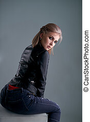 Sexy blonde sitting on grey cube poses half-turned