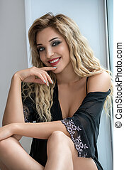 Sexy blonde sitting on window sill smiling