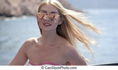 Sexy blonde with long hair in dress and sunglasses traveling aboard a boat in the sea