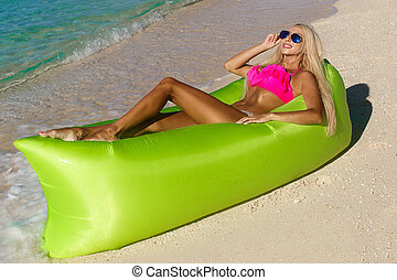 Sexy blonde with long hair resting on an inflatable banana...