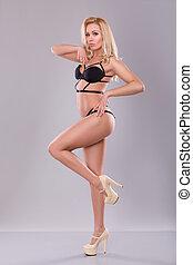 Sexy Blonde Woman In Black Bikini On Gray Background