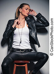 woman in leather clothes posing while sitting on a stool