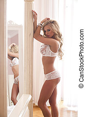 Sexy blonde woman in white lingerie