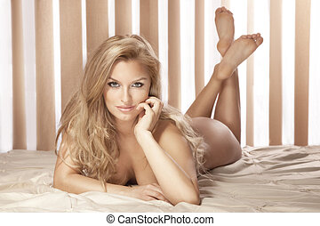 Sexy blonde woman lying naked on bed, looking at camera