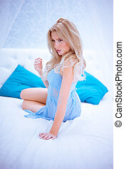 sexy blonde woman on bed - sensual blonde woman wearing blue...