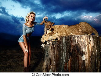 sexy blonde woman playing with lion cub on background with beautiful blue sky and storm clouds.