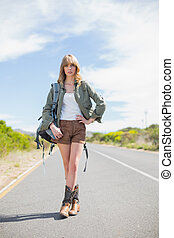 Sexy blonde woman posing while hitchhiking