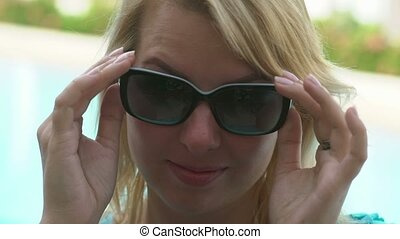 Sexy blonde woman removes sunglasses and wink