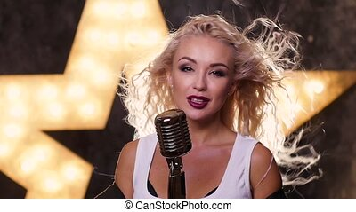 sexy blonde woman Singing with Retro Microphone, shining star in the background, slow motion, close up