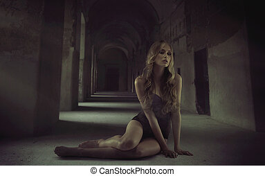 Sexy blonde woman sitting alone in the dungeon