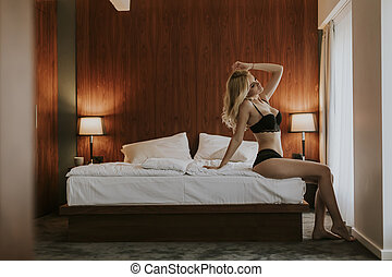 Sexy blonde woman sitting on bed