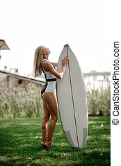 Sexy blonde woman standing with a wakeboard on green grass