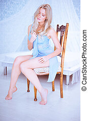 sexy blonde woman wearing blue lingerie sitting on the chair...