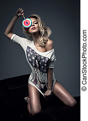 Sexy blonde woman with a lollipop in studio