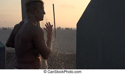 Sexy bodybuilder showering at the beach - Handsome muscular...