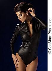 sexy, brünett, frau, in, leder, schwarze kleidung, aus, dunkler hintergrund