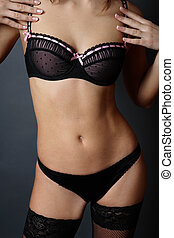 Sexy bra - Torso of slim woman in black thong, stockings and...