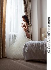 Sexy bride undressing in hotel room