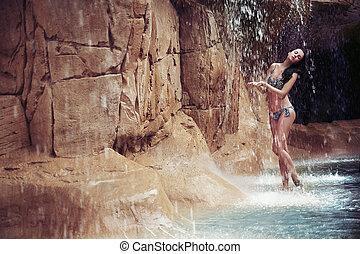 Sexy brunette enjoying jungle waterfall