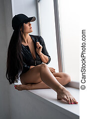 Sexy brunette in black baseball cap on window sill