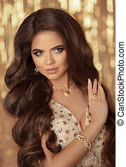 Sexy brunette in gold. Fashion Model present Golden Jewelry,...