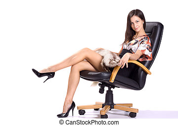 sexy brunette in mini with fur seat on armchair