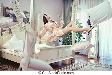 Sexy brunette lady levitating in her bedroom