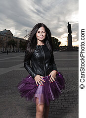 sexy brunette outdoors weared black leather jacket and ballet tutu-skirt violet color