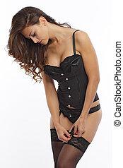 Sexy brunette adjusting her lingerie in studio environment