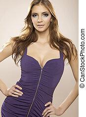 Sexy brunette posing in violet dress.
