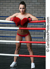 Sexy brunette posing topless in boxing ring