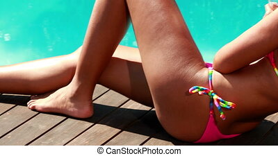 Sexy brunette relaxing poolside with cocktail on a sunny day