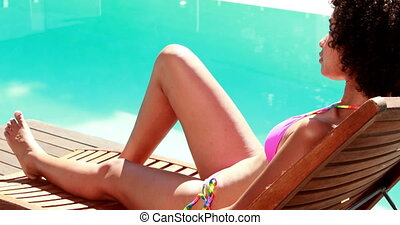 Sexy brunette sitting on deck chair poolside on a sunny day