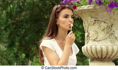 Sexy brunette stands in the Park and sucks lollipop