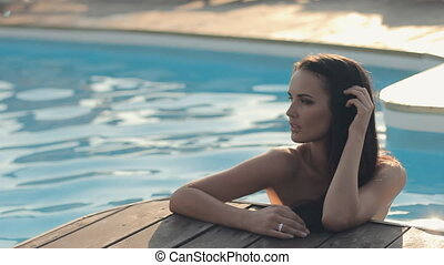 Sexy brunette with long hair in water in a swimming pool