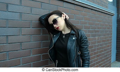 brunette with red lipstick in dark glasses and a leather jacket posing on camera near a wall
