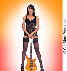 Sexy brunette with the guitar isolated on red