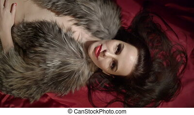 Sexy brunette woman covered with fur jacket lying on dark red silk satin bed