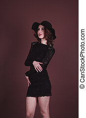 Sexy brunette woman in a black dress and hat