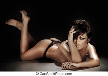 Sexy brunette woman lying and posing in lingerie on the...