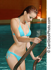 sexy brunette woman on pool ladder