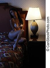 sexy brunette woman posing in bedroom