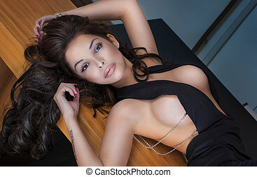 Sexy brunette woman posing, looking at camera.