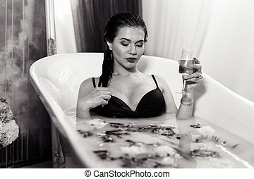 Sexy brunette woman relaxing in a hot bath with champagne
