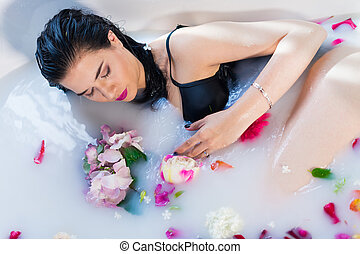 Sexy brunette woman relaxing in a hot bath with flowers