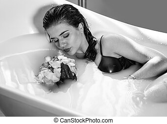 Sexy brunette woman relaxing in hot milk bath with flowers