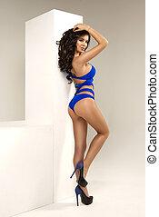 Sexy brunette woman wearing blue swimwear posing on white background. Perfect body