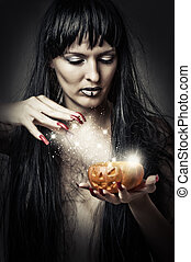 woman witch making magic to pumpkin