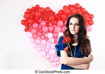 Sexy brunette woman with red heart balloons and flowers