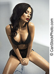 Sexy brunette woman with red lips in black lingerie